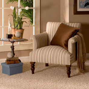 Upholstered chair and pillow on carpet in foyer.