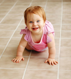 Little girl crawling on a fresh clean tile floor